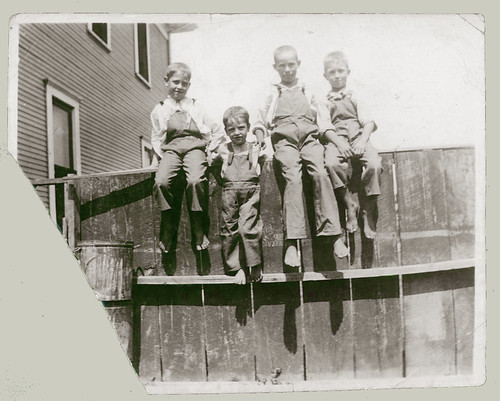 Four boys on a fence
