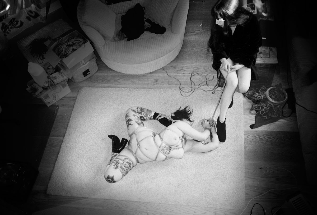 Contorted shibari floor bondage in a domestic setting