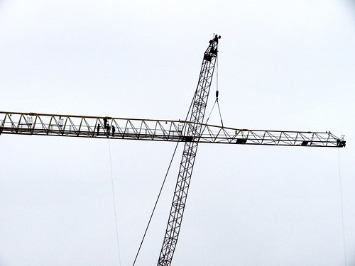 Workers starting the disassembly of a large construction crane. | by Bill A