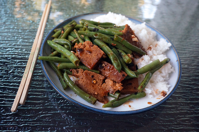 Green beans and seitan in black bean sauce, on blue-rimmed plate, the late-summer trees reflected in the background on the glass tabletop.