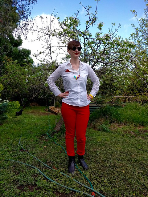 A woman stands in a garden, wearing a white button up shirt and red skinny pants.
