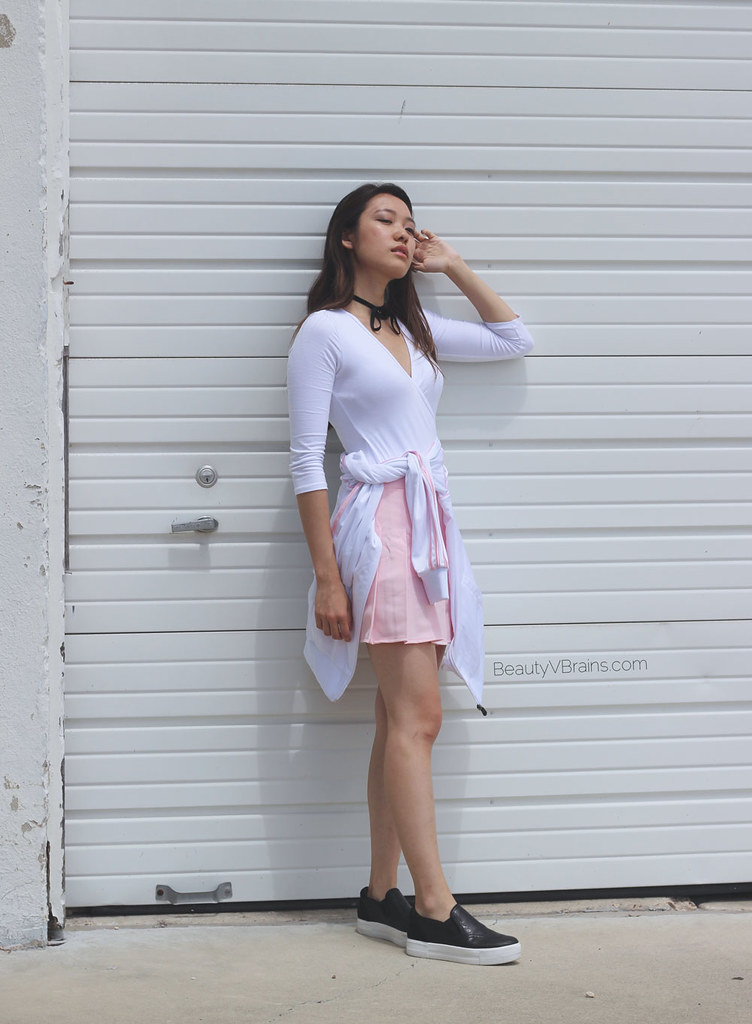 White wrap bodysuit and pink pleated mini skirt