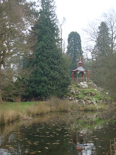 Oriental-style structure on rocky outcrop across a pond in Woburn Abbey Gardens