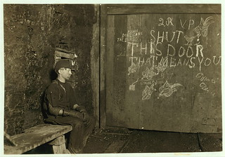 Vance, a Trapper Boy, 15 years old. Has trapped for several years in a West Va. Coal mine. $.75 a day for 10 hours work. All he does is to open and shut this door: most of the time he sits here idle, waiting for the cars to come ... (LOC) | by The Library of Congress