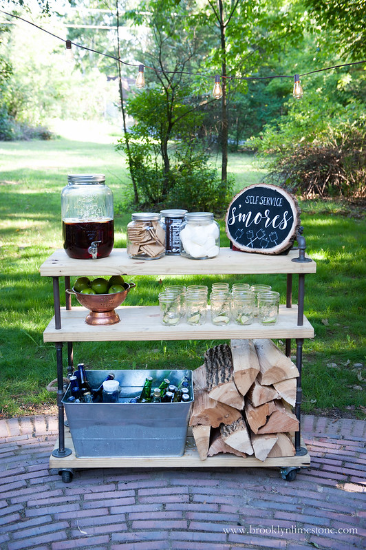 S'mores cart with wood slice sign, drink container, glasses, and s'mores supplies