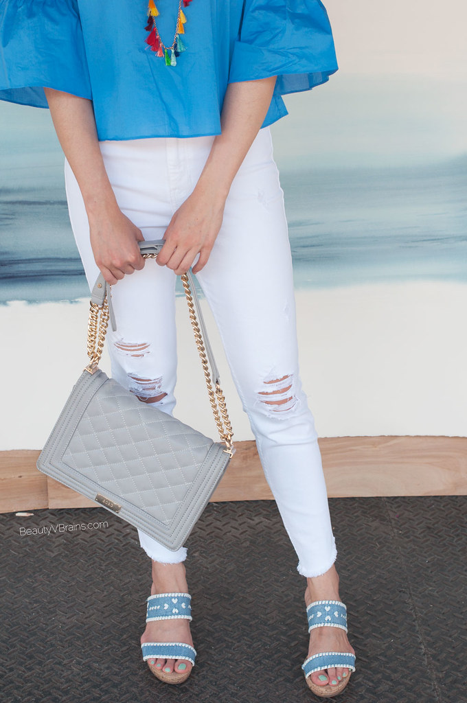 White destroyed knee ripped Hollister jeans and quilted gray bag