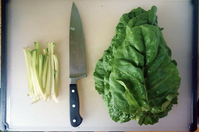 On a cutting board, a neat stack of crisp green leaves and another of their white stalks, separated by a large black-handled chef's knife