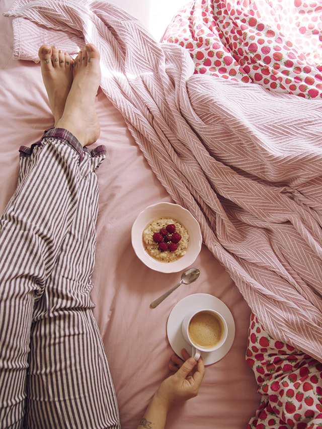 fresh Nespresso coffee and breakfast in bed cup and saucer pink blanket striped pyjamas