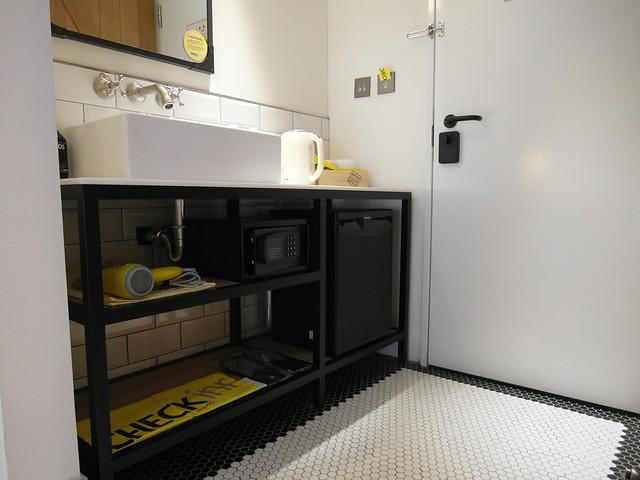 洗手台下方有吹風機、保險箱、洗衣袋、小冰箱@雀客旅館CHECK INN